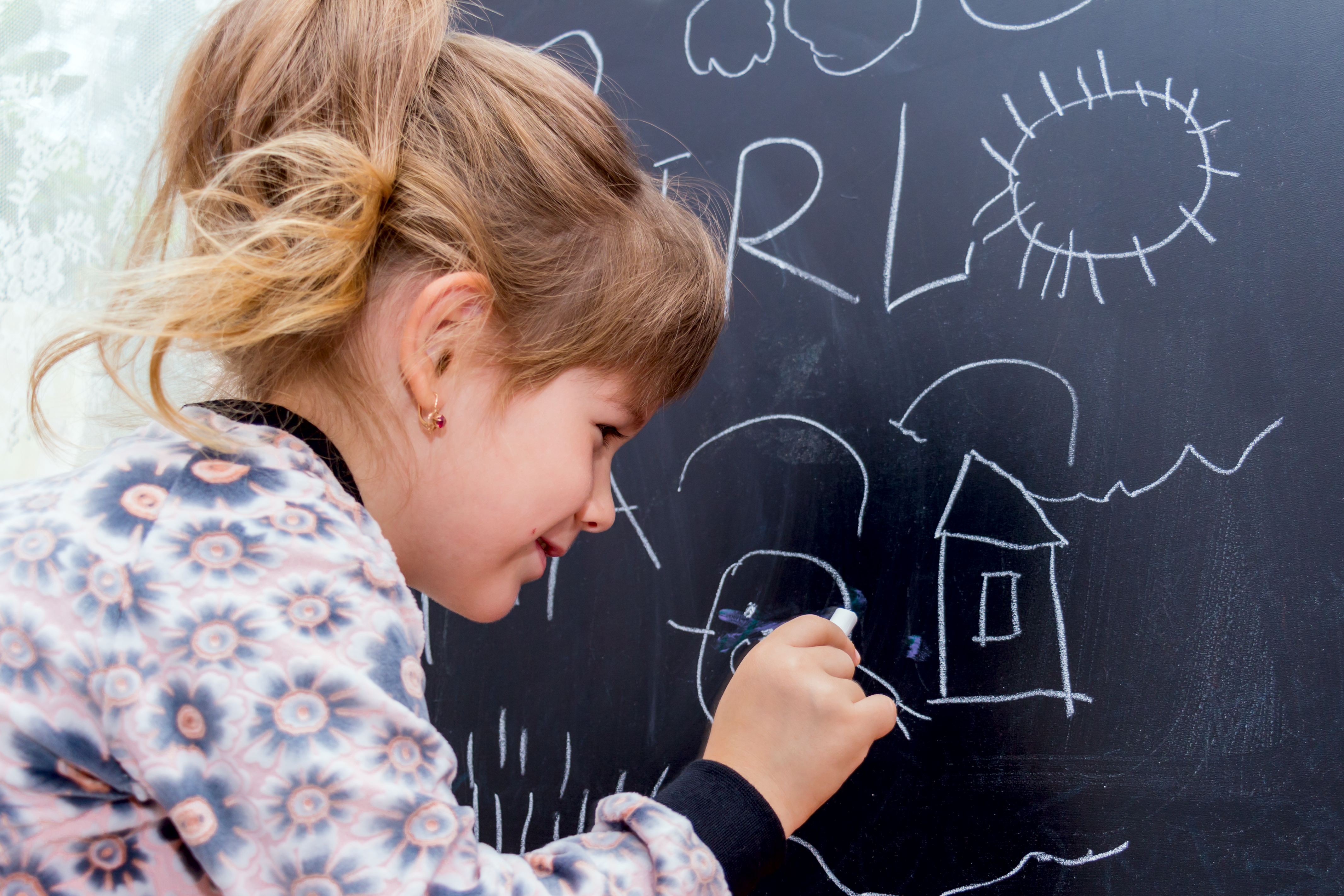 Little beautiful girl drawing on a blackboard. Learning at Home.