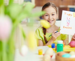 Smiling girl holding Easter greeting card